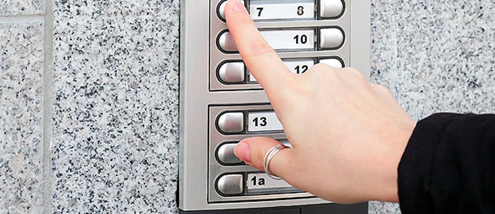 Stainless steel intercom keypad on brickwork
